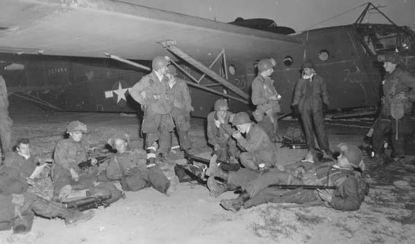 """Francja, 24 marca 1945 roku – żołnierze piechoty szybowcowej amerykańskiej 17. DPD przed wejściem na pokłady szybowców. W tle szybowiec CG-4A-WO o wojskowym numerze seryjnym 43-37494. Szybowiec na podwoziu kołowym nie dopuszczonym do lądowań w terenie przygodnym. Kąt przodowania tego typu podwozia, krotki nos szybowca bliski środka ciężkości, nagminne i bezprawne zmuszanie dowódców szybowców USAAF do przewozu ładunków daleko przekraczających maksymalną dopuszczalną masę startową, a w konsekwencji złe wyważenie całej konstrukcji powodowały to, że ten typ podwozia stanowił idealną oś obrotu CG-4A do kapotażu – rzecz nieznana w wojskowym szybownictwie brytyjskim. Sekcja ogonowa tego konkretnego egzemplarza szybowca 43-37494 jest przystosowana do zainstalowania spadochronu hamującego, który mógłby zadziałać także jako element przeciwkapotażowy, lecz szybowiec nie ma tego spadochronu, gdyż przez całą wojnę dostarczano ich za mało. W czasie wojny amerykański miesięcznik techniki lotniczej """"Air Tech"""" dwukrotnie pisał, że CG-4A musi lądować w warunkach bojowych normalnie, czyli na płozach, jak nakazywały to także instrukcje wykonywania lotów tym typem szybowca, ale europejskie USAAF nie zamówiły tzw. podwozia taktycznego dla CG-4A i lądowały tymi szybowcami w warunkach bojowym na tzw. podwoziu szkolnym, które widać na fotografii. Liczbę ofiar kapotaży CG-4A – czyli ofiar nie bojowych, poniesionych wyłącznie z winy urzędników – zatuszowano i wszystkie one występują w którejś z siedmiu kategorii strat bojowych. Fot. US Army"""